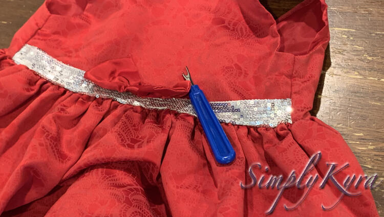 Image shows the center half of a fancy red dress with a white and silver sequined section along the front of the waist. On the center is a mostly removed red bow with a blue handled seam ripper laid out beside it.