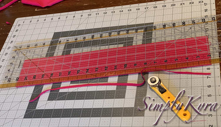 Image shows the pink strip measuring twenty by 3.25 inches now. The excess thin strip is cut off the edge with a yellow rotary blade off to the side.