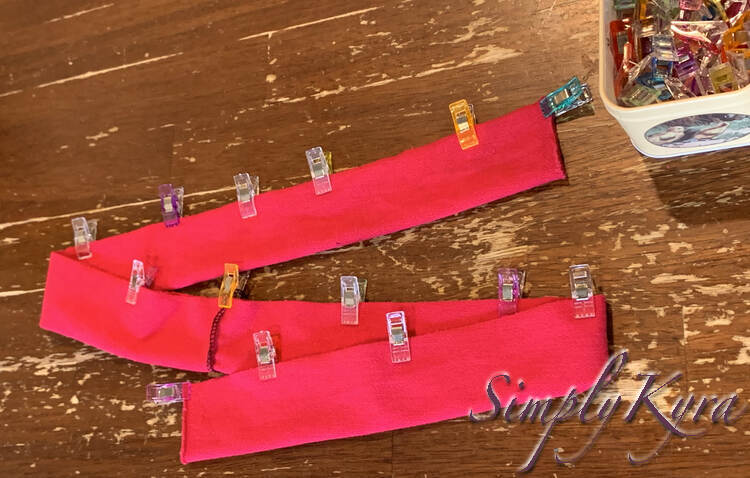 Image shows the strip folded twice to fit in the shot. Along the raw edge there's multicolored sewing clips to hold it in place.