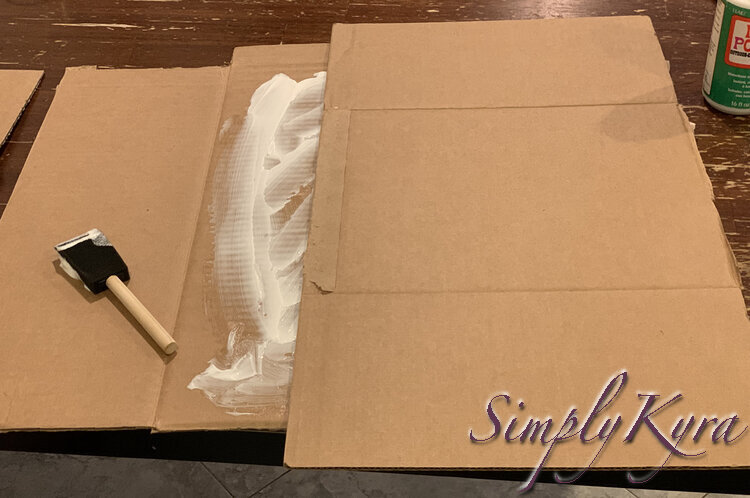 Image shows the white Mod Podge extending from where the other box is laid out overtop of it. The white smeared foam brush is to the left.