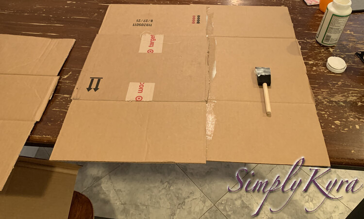Image shows a large square of box composed of two Target box sections with a Mod Podge smeared foam brush on top of them.