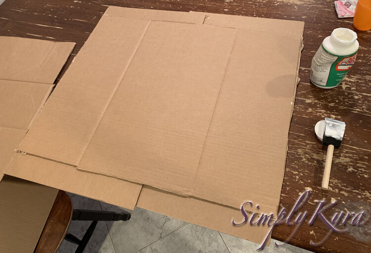 Image shows the same vague rectangle of cardboard but this time it's three layers tall with the smaller Target boxes peeking out from the front and back. The almost empty jar of Mod Podge and the wet brush sit to the right side of the photo.