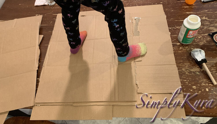 Image shows Zoey's lower half, with unicorn pants and bright sock, standing on the previous showing cardboard as if it was already a skateboard.