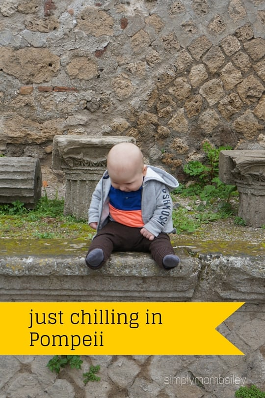 baby boy sitting on a wall in pompeii italy