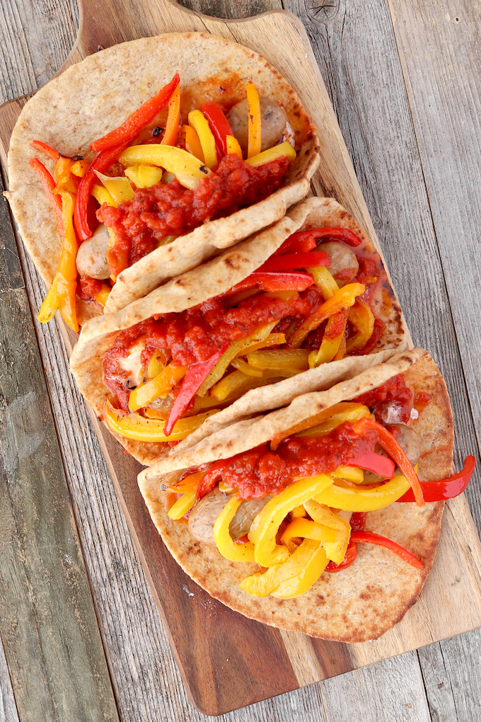 Sheet Pan Italian Sausage Gyros are simple to make, requiring just 10 minutes hands on prep. Spicy Italian Chicken Sausage, tender roasted red bell peppers and sweet onions wrapped in a whole-wheat pita with melty mozzarella and marinara.