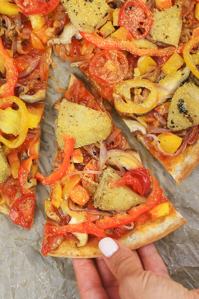 "Homemade Veggie Pizza (V, GF) is made with an herby spelt-flour crust, simple tomato sauce, LOADS of sautéed veggies and topped with a ""secret"" ingredient."