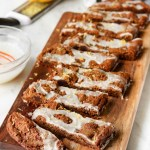 Thick, soft and chewy iced gingerbread bars are studded with dark chocolate chunks and topped off with a simple glaze and hint of lemon. Perfect for the holidays!