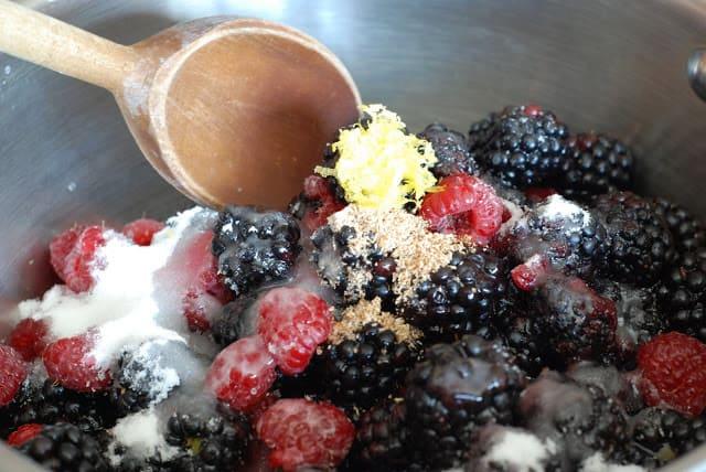 berries, sugar, lemon zest, nutmeg, being stirred together in sauce pan with wooden spoon