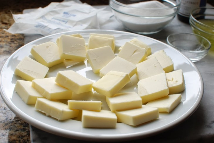 butter cut into squares stacked on a white plate