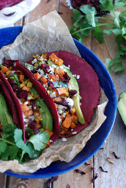 two veggie tacos with hibiscus tortillas on blue plate