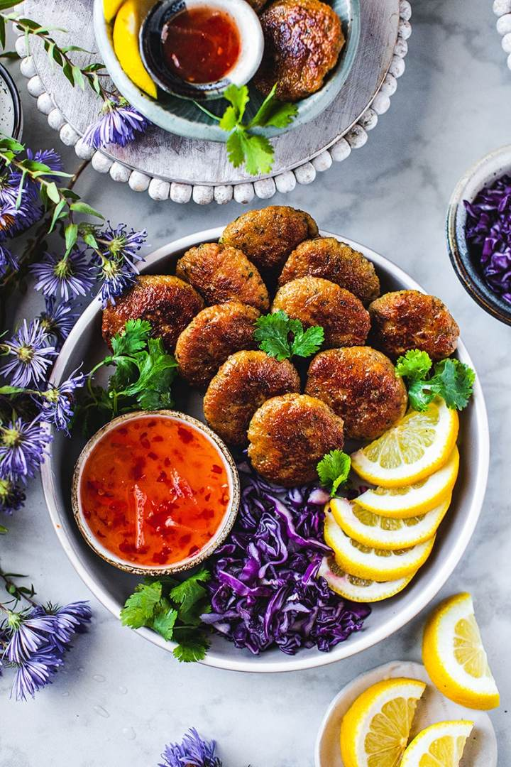 Thai shrimp cakes are very tasty appetizers with very memorable flavors that come from fresh ingredients used in this recipe. With the use of fresh ingredients like garlic, shallots, kaffir lime leaves, lime juice, cilantro stems, and ground white pepper, this Thai starter will leave you wanting more. #thaishrimpcake #todmungoong #thaishrimpcakewithchilisauce #thaiappetizer