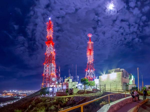 Fotografía nocturna de las torres de las televisoras iluminadas y la luna en el Cerro de la Memoria