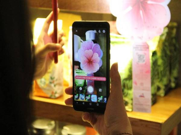 Untuk menyaksikan keajaiban guna teknologi AR camera Facebook dengan scan barcode di atas lambang bunga sakura.