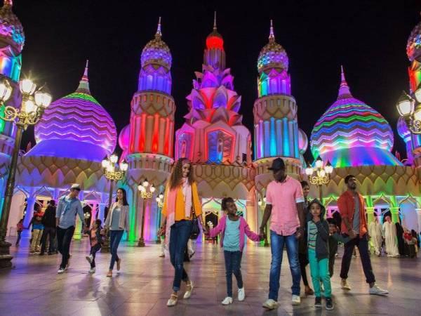 GLOBAL Village yang berwarna-warni dengan neon pada waktu malam.