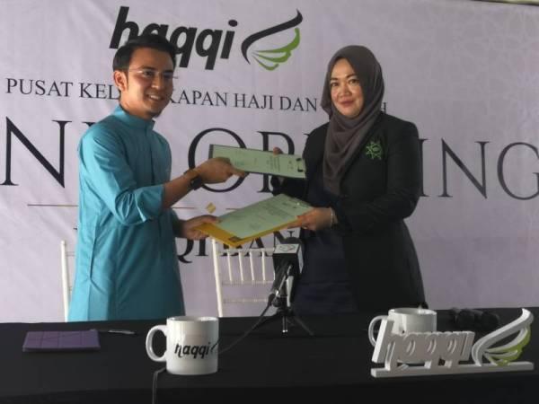 MOHAMAD Fitri (kiri) dan Noorsamah bertukar-tukar dokumen memorandum persefahaman pada majlis pelancaran Butik Haqqi 2020 di Bandar Baru Bangi pada hari ini.