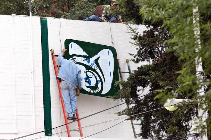 Trabajador coloca el logo del IMSS en el edificio que se construyó a marchas forzadas. Foto: Francisco Cañedo, SinEmbargo