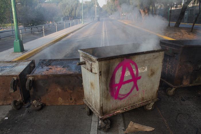 El tránsito para ingresar al circuito escolar en el punto está impedido por una barricada de contenedores de basura, los cuales también fueron quemados. Foto: Cuartoscuro.