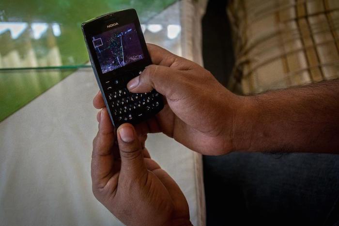 El comisario Eduardo Macedo revisa su teléfono y recuerda con nostalgia el pueblo de que fue expulsado. Foto: Daniel Ojeda/VICE.