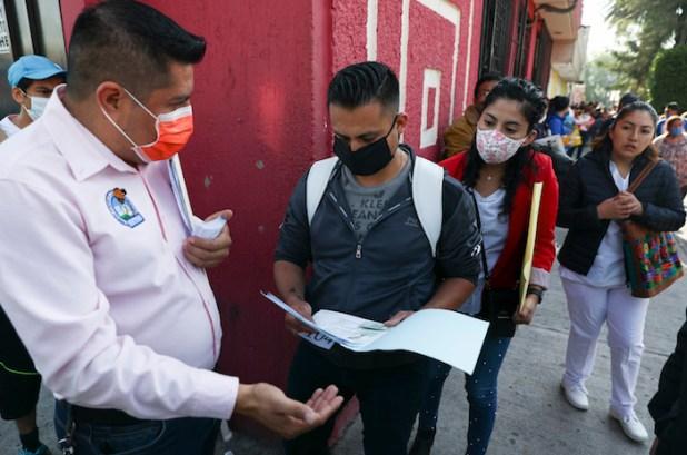 Un trabajador revisa los documentos de un hombre que solicita un trabajo médico fuera del sindicato nacional de trabajadores de la salud en la Ciudad de México, el martes 14 de abril de 2020.