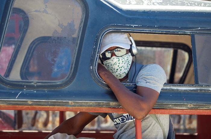 Una persona con mascarilla se sienta en un vehículo este lunes, primer día en que su uso es obligatorio, en Puerto Príncipe (Haití).