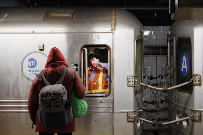 Un empleado de la Autoridad Metropolitana del Transporte (MTA) espera en el área de conductores de un vagón del metro mientras agentes de la policía de Nueva York y la MTA despiertan a pasajeros dormidos y los dirigen a la salida de la estación 207th Street A-train el jueves 30 de abril de 2020 en Manhattan, Nueva York.