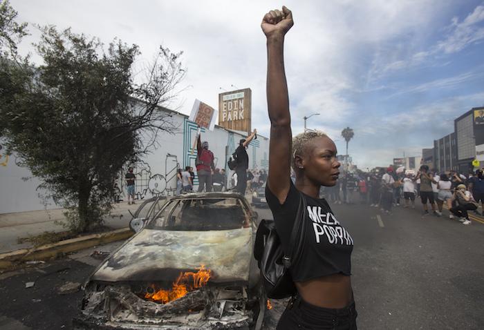 Una manifestante posa para la prensa ante un vehículo policial en llamas en Los Ángeles, el sábado 30 de mayo de 2020, durante una manifestación por la muerte de George Floyd, un hombre afroamericano que murió tras ser detenido por la policía en Minneapolis, el 25 de mayo de 2020.