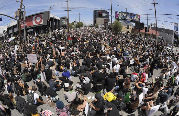 En esta imagen tomada con un gran angular, manifestantes sentados en un cruce durante una protesta por la muerte de George Floyd, un hombre afroamericano que murió tras ser detenido por la policía en Minneapolis, el sábado 30 de mayo de 2020 en Los Ángeles.