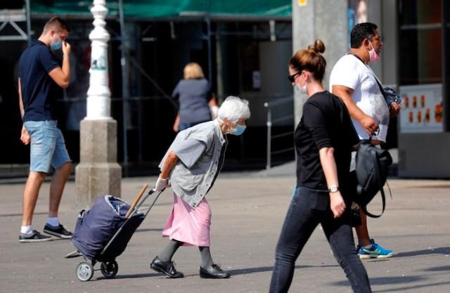 Varias personas con mascarilla caminan por la calle en Zagreb, Croacia.