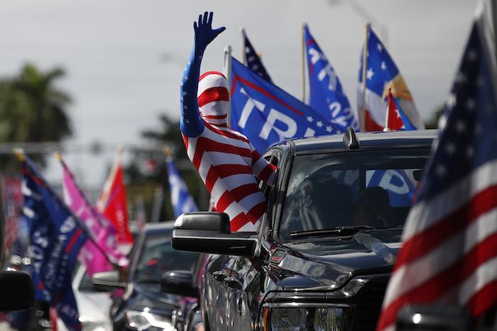 Un hombre vestido con un traje de la bandera estadounidense saluda el domingo 1 de noviembre de 2020 antes de que arranque una caravana de vehículos en el Tropical Park en apoyo al Presidente Donald Trump, en Miami.