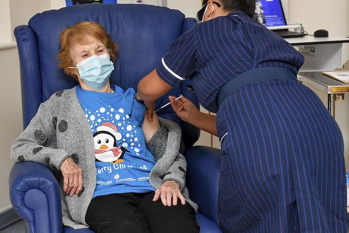 Margaret Keenan, de 90 años, recibe la primera dosis suministrada en Gran Bretaña de la vacuna de Pfizer-BioNTech contra la COVID-19, administrada por la enfermera May Parsons en el Hospital Universitario de Coventry, Inglaterra, el martes 8 de diciembre de 2020.