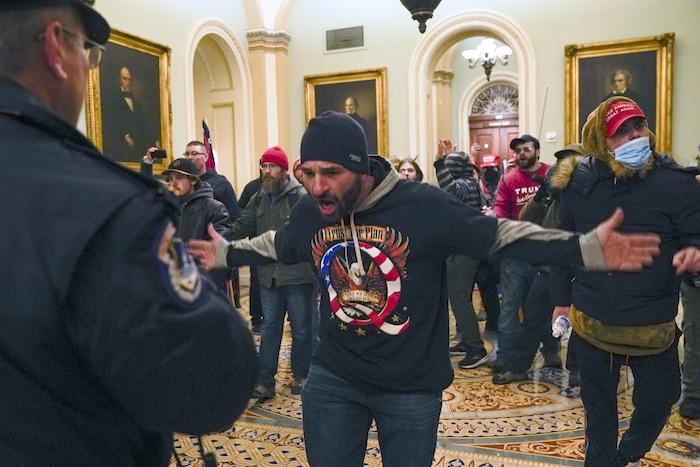 Simpatizantes del Presidente Donald Trump se enfrentan a la policía del Capitolio en el pasillo afuera del recinto del Senado, el miércoles 6 de enero de 2021, en Washington.