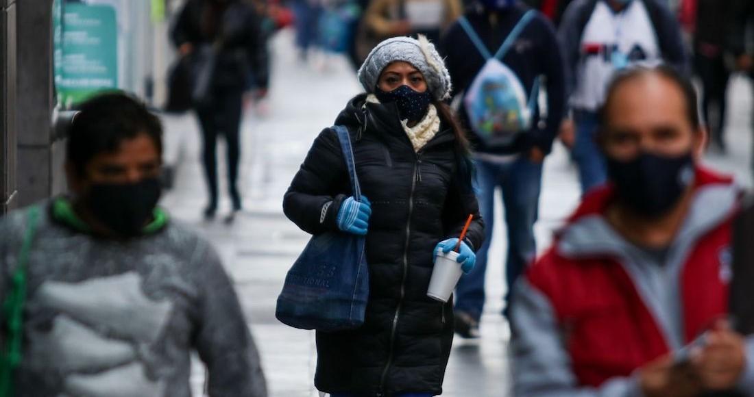 Personas con cubrebocas, chamarras y guantes transitan por el primer cuadro de la Ciudad de México
