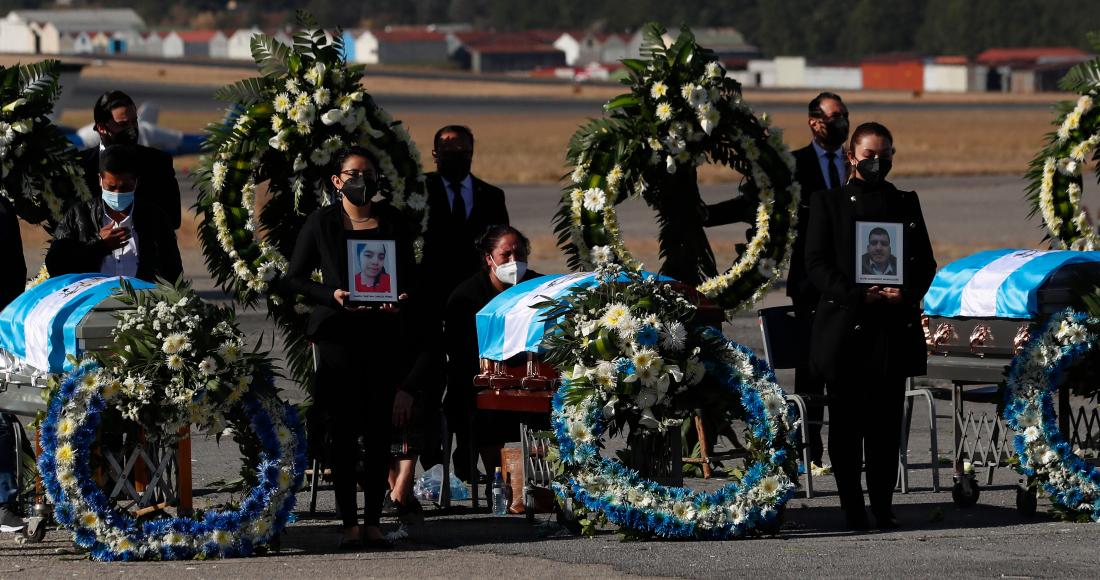 La gente espera de pie con fotografías mientras los restos de 16 migrantes guatemaltecos que fueron asesinados cerca de la frontera entre Estados Unidos y México en enero llegan a la base de la Fuerza Aérea en la Ciudad de Guatemala, el viernes 12 de marzo de 2021.