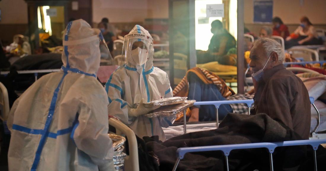 Un trabajador de salud distribuye paquetes de comida dentro de un centro de cuarentena para pacientes con COVID-19, en Nueva Delhi, India, el lunes 19 de abril de 2021.