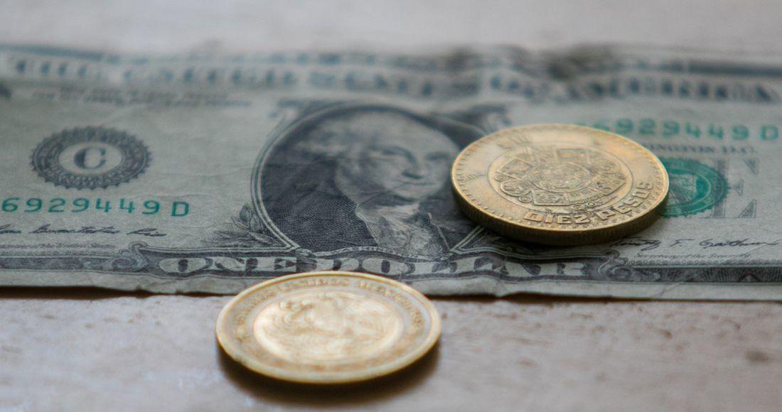 foto monedas mexicanas sobre un dolar