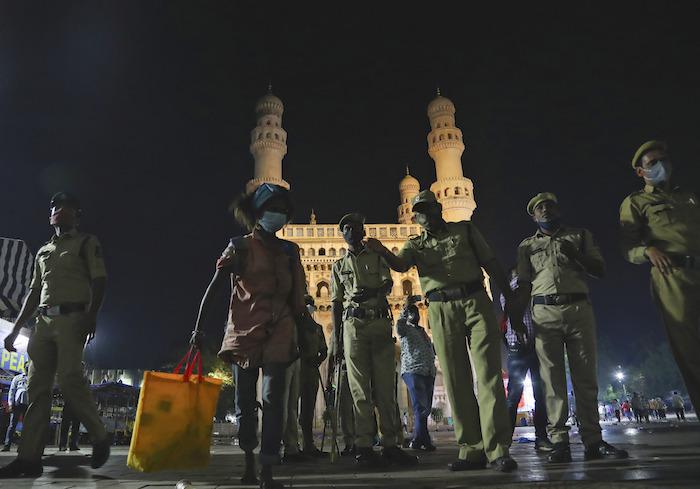 Unos agentes de la policía india despejan una calle durante un toque de queda impuesto por Gobierno estatal, el martes 20 de abril de 2021, en Hyderabad, India.