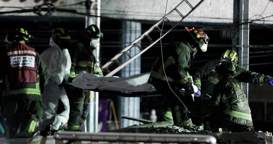 Bomberos trasladan el cuerpo de una víctima del derrumbe de una estructura del Metro de la Ciudad de México, ocurrida en la Línea 12.