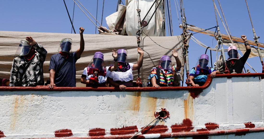 En esta foto del 30 de abril del 2021, una delegación del Ejército Zapatista de Liberación Nacional saluda desde el barco que les llevará a Europa en ocasión del 500mo aniversario de la Conquista de México, desde Isla de Mujeres, en el estado de Quintana Roo.