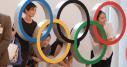 Gente posa con los anillos olímpicos en Tokio.