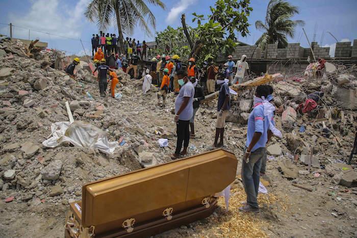 Decenas de personas permanecen de pie el miércoles 18 de agosto de 2021 , en Les Cayes, Haití, junto a un ataúd con los restos de François Elmay, cuyo cadáver fue recuperado entre los escombros de una casa destruida por un terremoto de 7.2 grados.