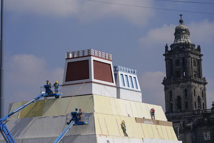 Operarios construyen una réplica del Templo Mayor azteca, con una imagen del dios precolombino Quetzalcoatl adornando los edificios colindantes, en la Plaza del Zócalo, en Ciudad de México, el 9 de agosto de 2021.