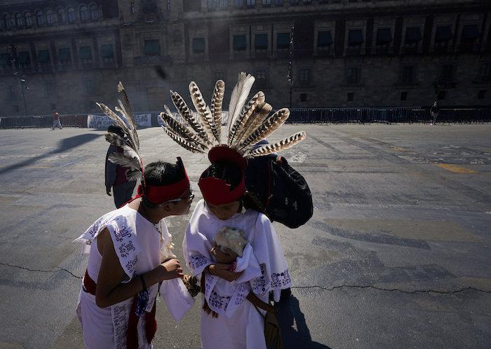 Dos jóvenes charlan antes de participar en la conmemoración del 700 aniversario de la fundación de la ciudad azteca de Tenochtitlan, hoy conocida como Ciudad de México, en la Plaza del Zócalo, en la Ciudad de México, el 26 de julio de 2021, en plena pandemia del coronavirus.