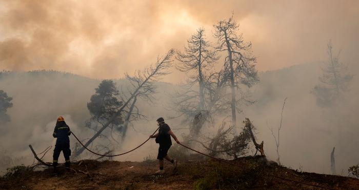 En imagen de archivo del lunes 9 de agosto de 2021, un bombero combate las llamas al tiempo que un civil sostiene una manguera durante un incendio forestal en la aldea de Ellinika, en la isla de Evia, aproximadamente a 176 kilómetros (110 millas) al norte de Atenas.