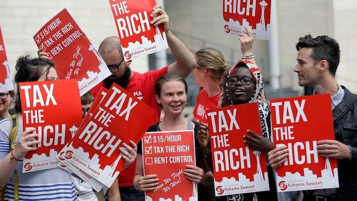 Los manifestantes muestran carteles en apoyo del nuevo impuesto sobre la renta de la ciudad de Seattle para los residentes adinerados.