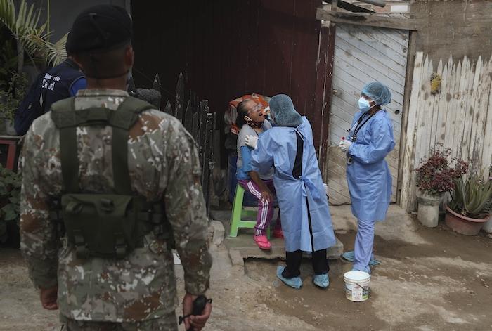 Escoltados por un soldado, dos médicos toman una muestra a Juana Bovadilla, de 79 años, durante una campaña de pruebas diagnósticas contra la COVID-19 en el barrio Villa María del Triunfo, el martes 12 de enero de 2021, en Lima, Perú.