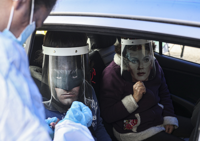 Un trabajador de la salud realiza una prueba rápida de COVID-19 a Ignacio Poblete, con un protector facial con la imagen de Batman, acompañado de su madre Marisol Aro, usando un protector facial con la imagen de la Mujer Maravilla, en Santiago, Chile, el sábado. 27 de junio de 2020.