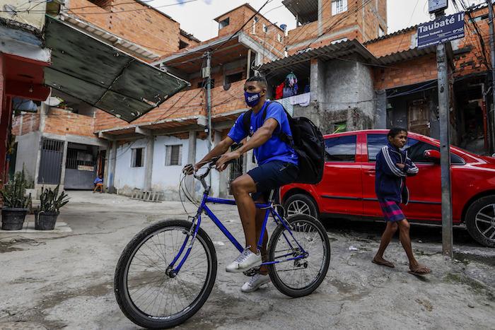 Jonathan Arcanjo, repartidor de la empresa Favela Brasil Xpress, circula en bicicleta por los callejones de la favela Paraisópolis de Sao Paulo, Brasil, para entregar un paquete el martes 31 de agosto de 2021, en medio de la pandemia de COVID-19.
