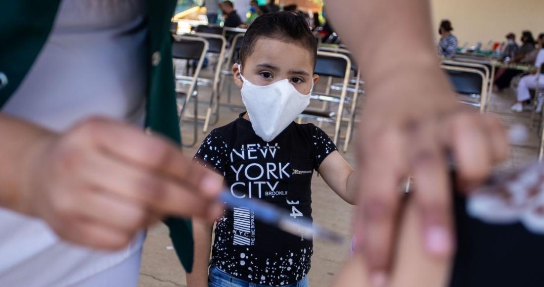 Niño observa la inmunización de su madre en el modulo de vacunación del municipio de Morelos, Zacatecas.