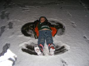 Kaleb in the driveway making a snow angel