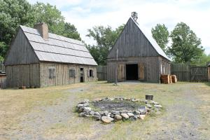 a settlement - neat log/board houses, trimmed grass, and rock fire pit